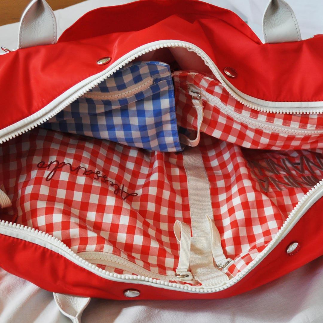 """Dettaglio dell'interno della borsa mamma Solferina piena di sacchetti cambio """"Tate"""" multicolor"""